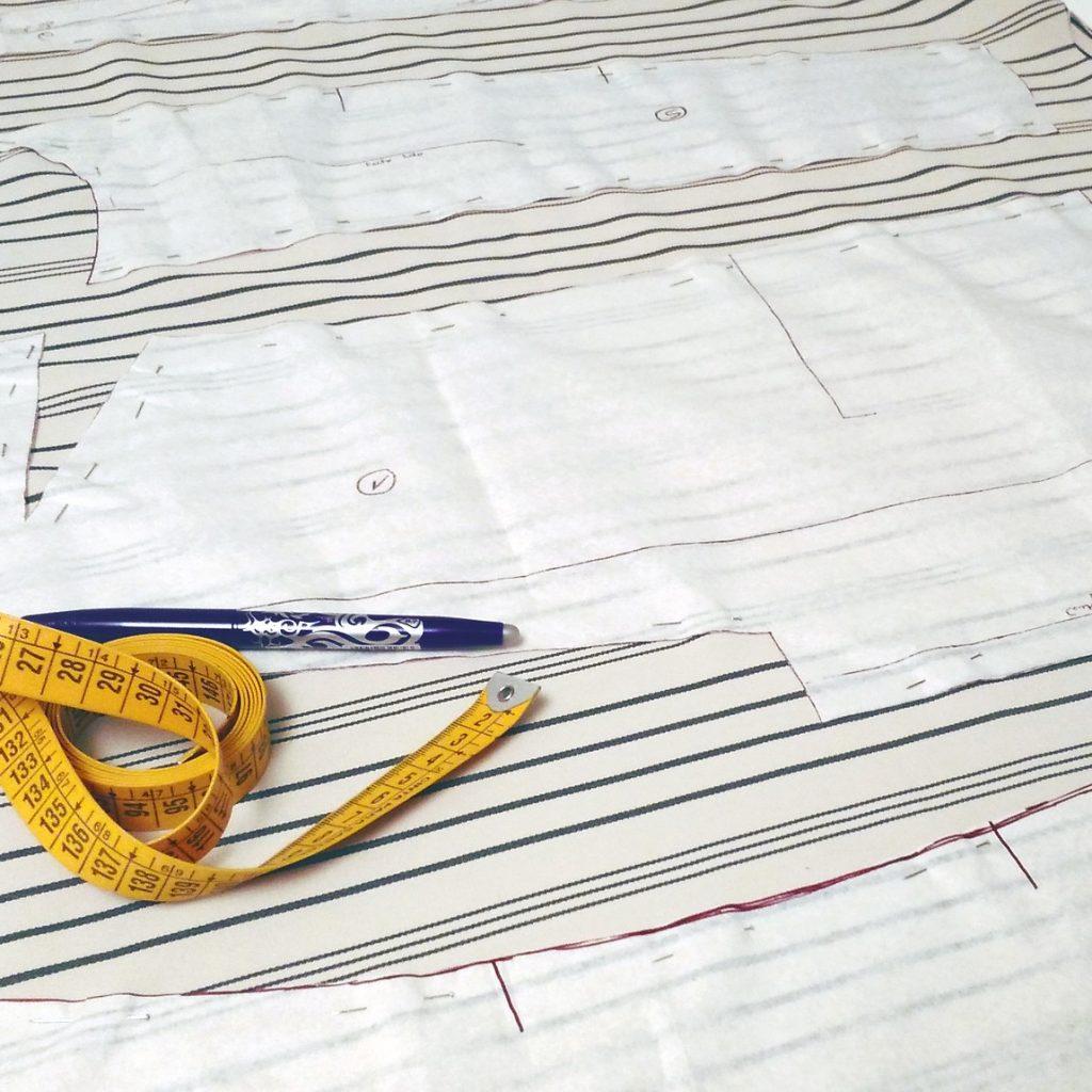 moldes para corte de uma blusa sobre tecido listrado