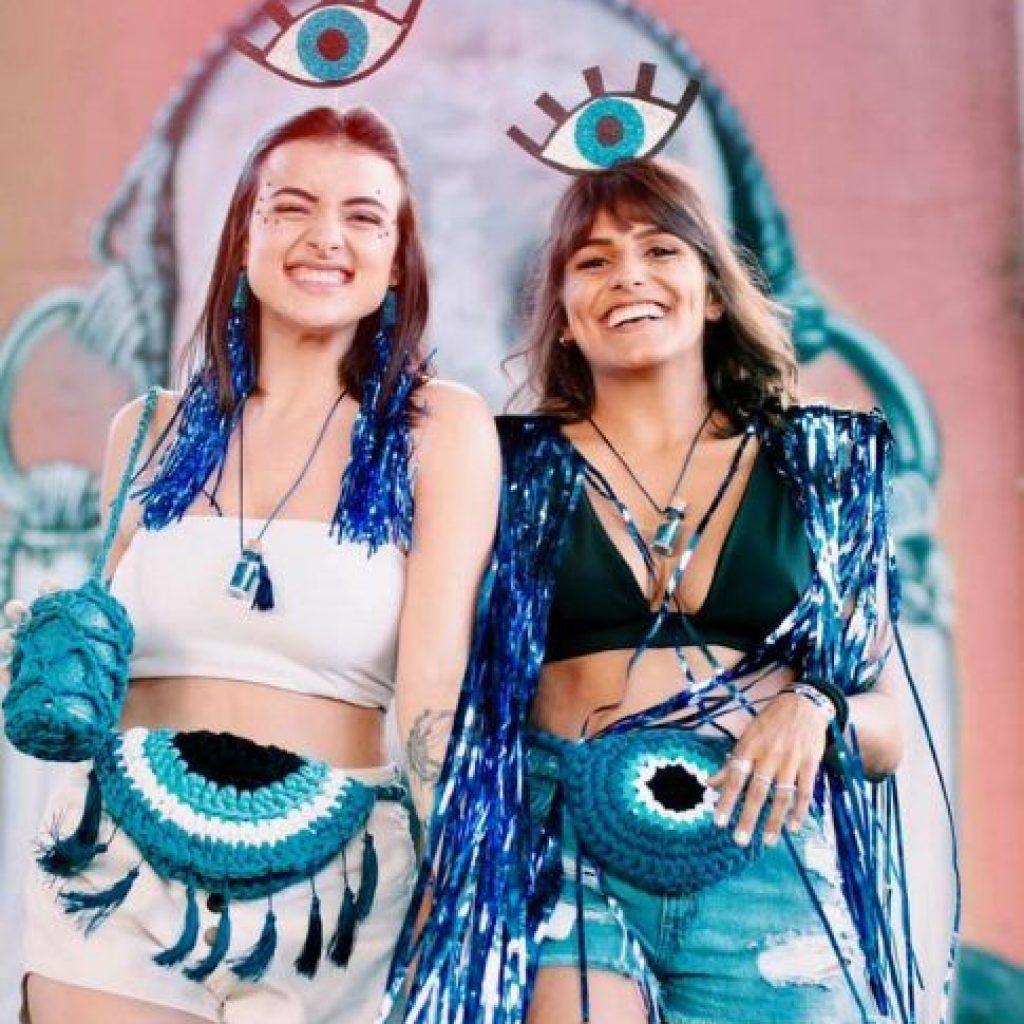 look carnaval com tema olho grego. composto com top, short, tiara, pochete de crochê, brinco de fitas longas, obreiras, tenis, e pingente de garrafinha
