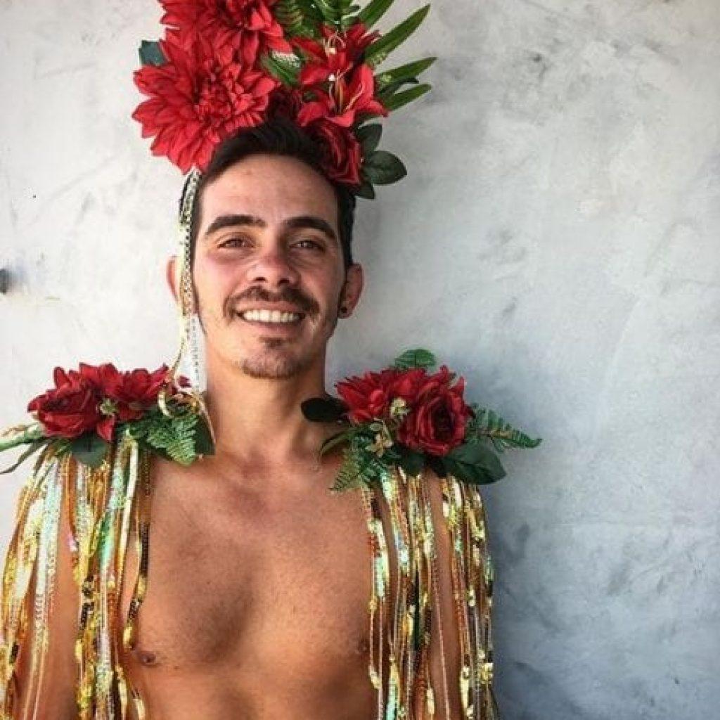 look masculino com arranjo de cabeça floral e ombreiras com fitas e arranjos florais.
